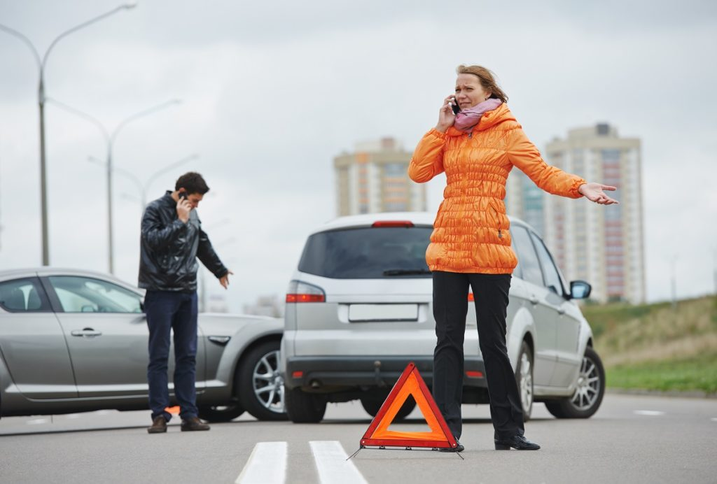 People involved in a car accident calling using smartphones