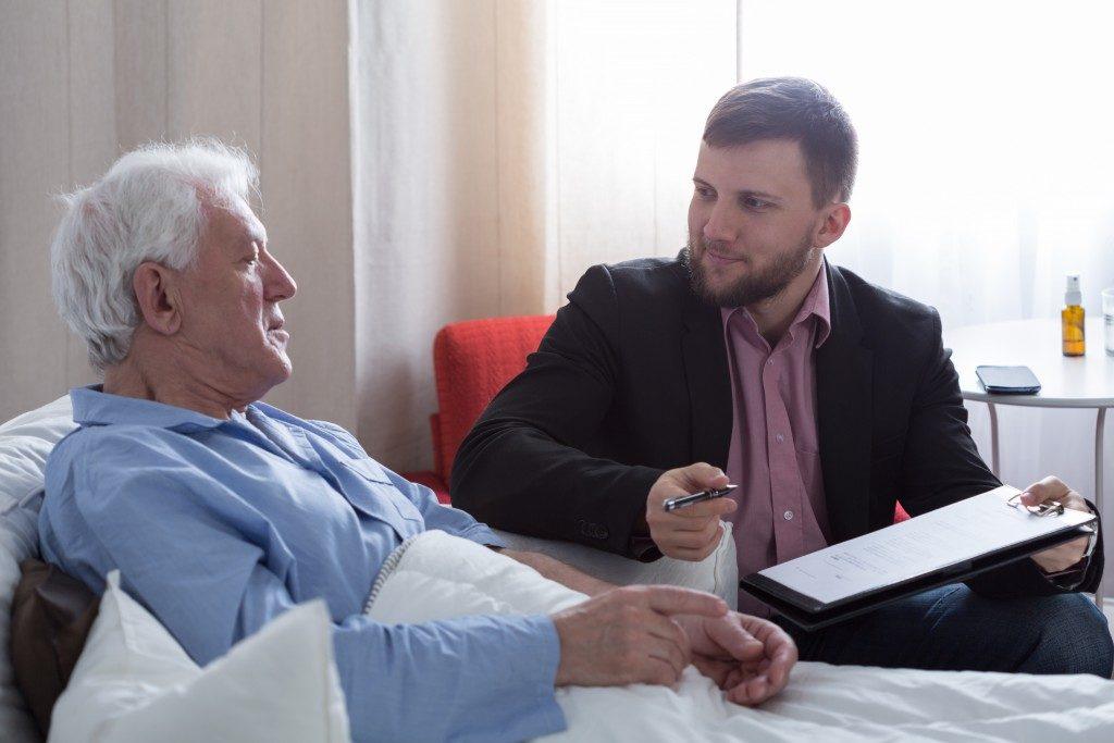 Elderly man in hospital with legal adviser