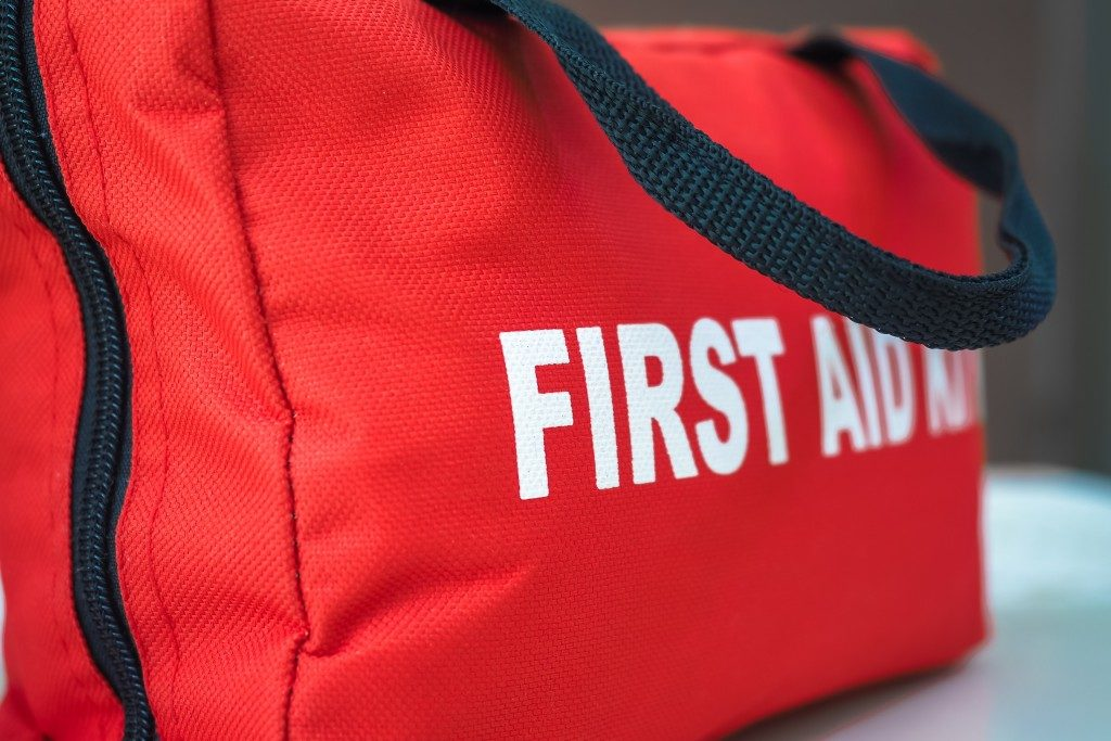 red first aid kit bag with a black zip and handle, in closeup