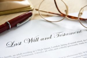 last will and testament paper with pen and reading glasses