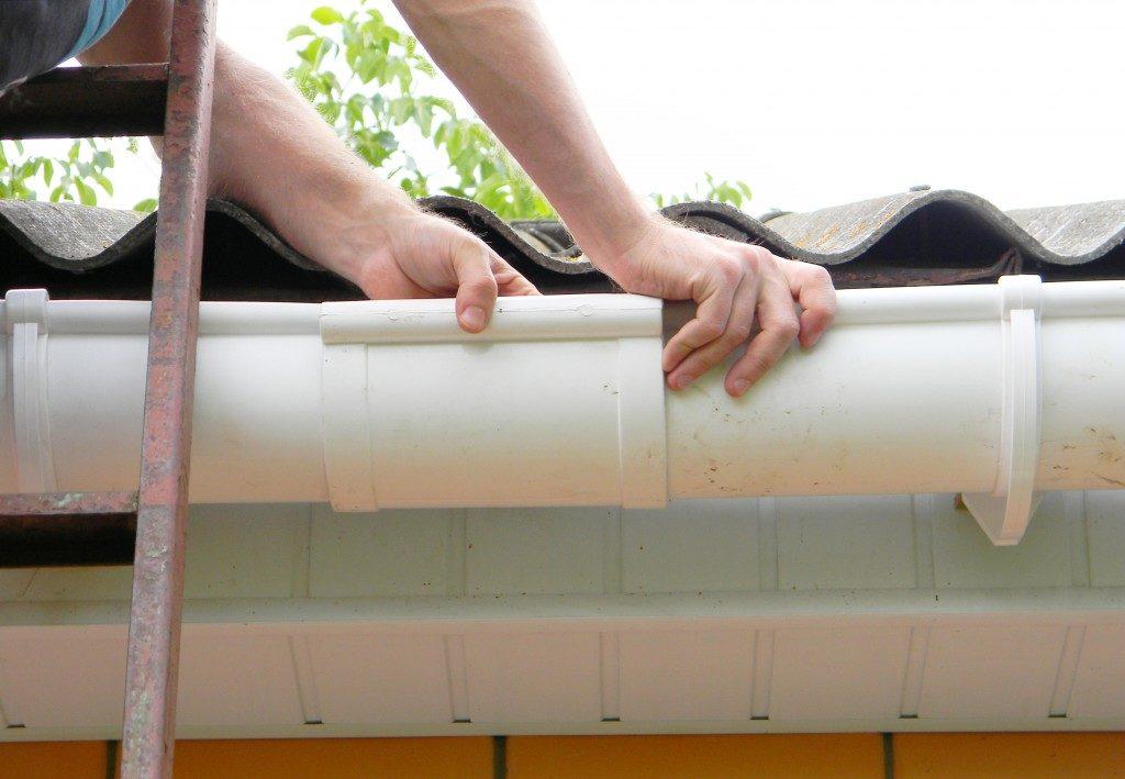 Man installing plastic roof gutter