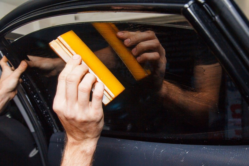 man cleaning a tinted car window
