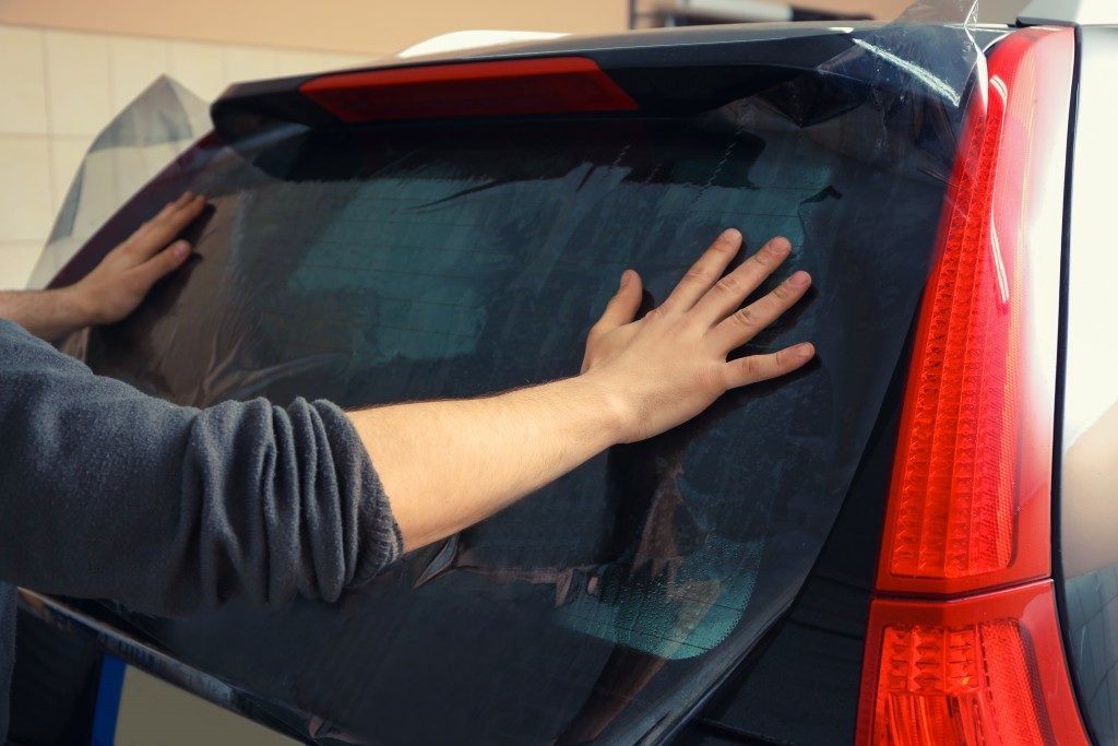 man tinting his car window
