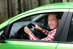 man ndriving green car