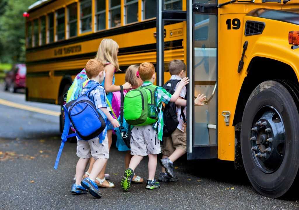group of young children getting on the schoolbus