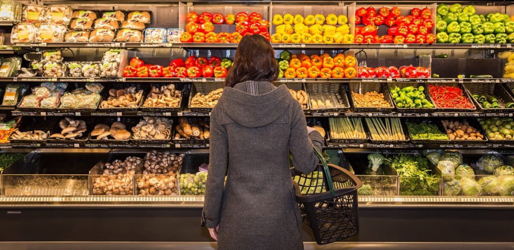woman looking at fresh produce at the grocery store