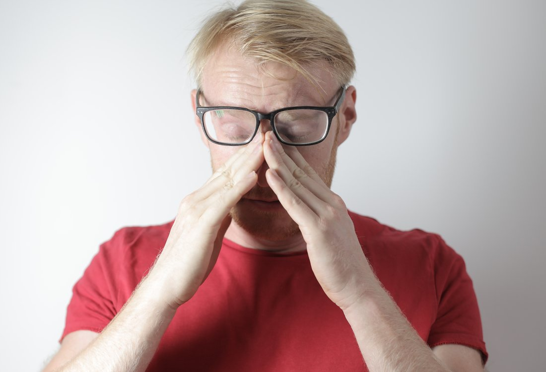 man rubbing nose bridge and getting anxious