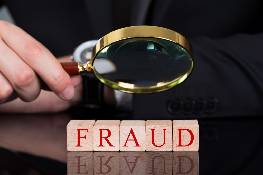 young businessman examining Fraud blocks through magnifying glass