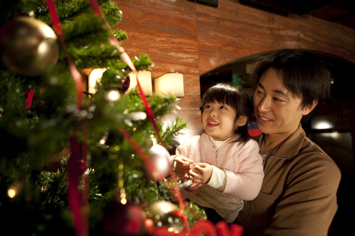 father holding his daughter in front of a christmas tree