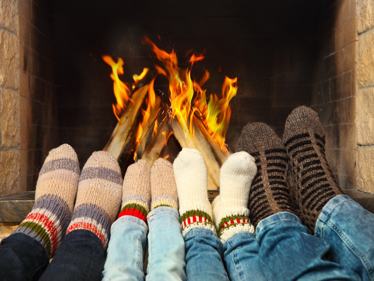 wearing socks infront of a fireplace