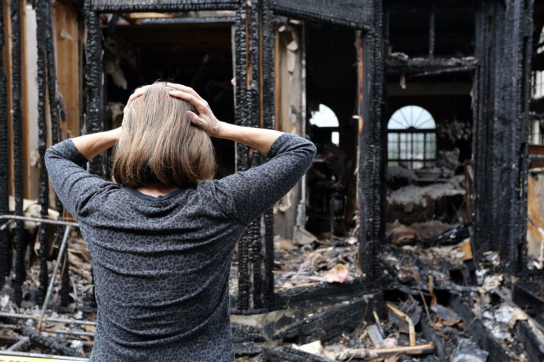 woman in shock in front of burnt down house