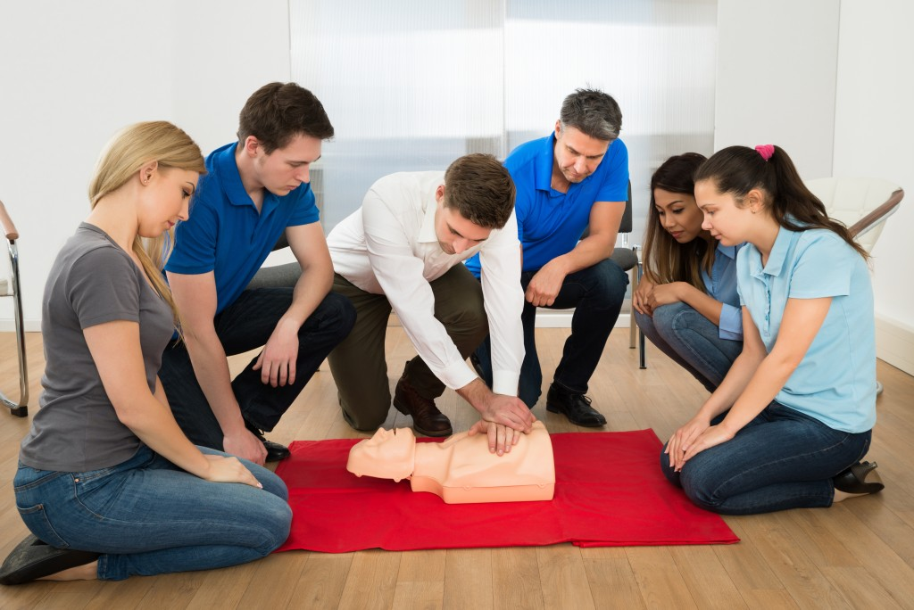 group of people practicing cpr on a dummy