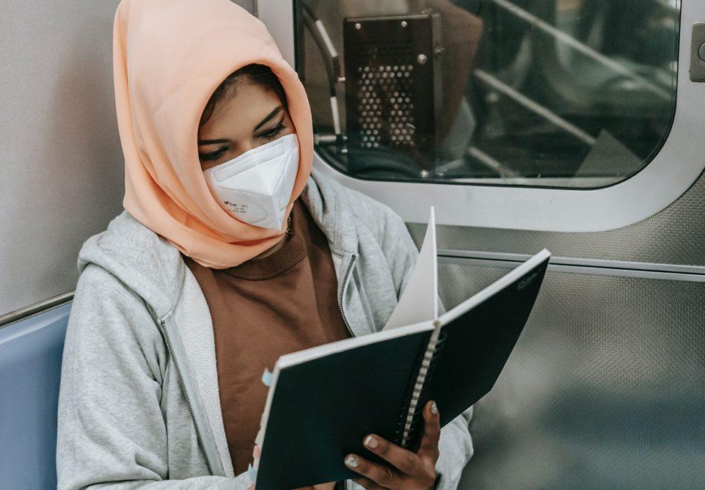 a woman wearing a mask at the subway